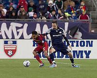 Real Salt Lake forward Paulo Araujo Jr. (23) dribbles as New England Revolution defender Ryan Cochrane (45) defends. In a Major League Soccer (MLS) match, Real Salt Lake defeated the New England Revolution, 2-0, at Gillette Stadium on April 9, 2011.