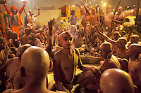 "India. Uttar Pradesh state. Allahabad. Maha Kumbh Mela. Hindu holy men of the Juna Akhara sect participate in rituals that are believed to rid them of all ties in this life and dedicate themselves to serving God as ""Naga"" or naked holy men. A group of Naga Sadhus with a seer dressed with orange clothes and turban at night in Sangam. The Kumbh Mela, believed to be the largest religious gathering is held every 12 years on the banks of the 'Sangam'- the confluence of the holy rivers Ganga, Yamuna and the mythical Saraswati. The belief is that bathing and taking a holy dip will wash and free one from all the past sins, get salvation and paves the way for Moksha (meaning liberation from the cycle of Life, Death and Rebirth). In Hinduism, Sadhu (good; good man, holy man) denotes an ascetic, wandering monk. Sadhus are sanyasi, or renunciates, who have left behind all material attachments. They are renouncers who have chosen to live a life apart from or on the edges of society in order to focus on their own spiritual practice. The significance of nakedness is that they will not have any worldly ties to material belongings, even something as simple as clothes. This ritual that transforms selected holy men to Naga can only be done at the Kumbh festival. A Sadhu is usually referred to as Baba by common people. The Maha (great) Kumbh Mela, which comes after 12 Purna Kumbh Mela, or 144 years, is always held at Allahabad. Uttar Pradesh (abbreviated U.P.) is a state located in northern India. 6.02.13 © 2013 Didier Ruef"