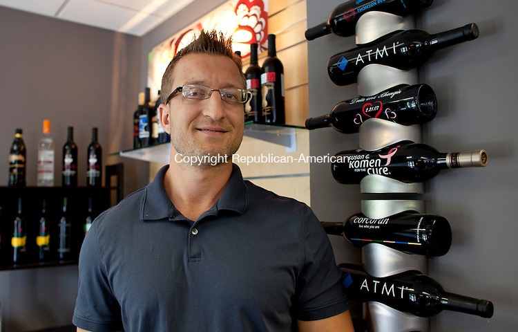 WATERTOWN, CT-28 June 2013-062813BF03-  Afrim Pocesta owner of Engraved Products Co. in Watertown stands in front of a display of the etched bottles his company produces for corporate and private clients. Pocesta is a Macedonian immigrant. Bob Falcetti Republican-American