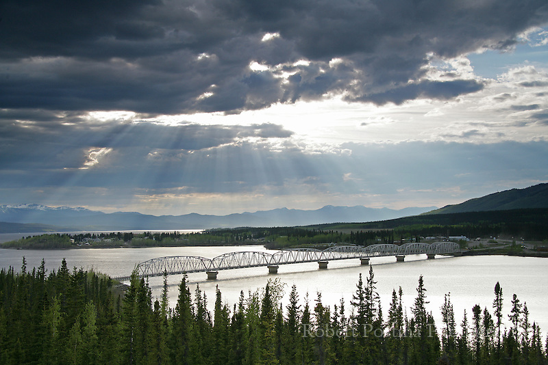 Rays of sun shining through the clouds over Teslin, Yukon. Teslin bridge over Nisutlin Bay.