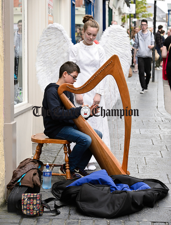 "Heavenly Music...Antone Fox of Belfast is watched by ""Angel"" Neidin Mooney of Ennis as he plays harp during Fleadh Cheoil na hEireann in Ennis. Photograph by John Kelly."