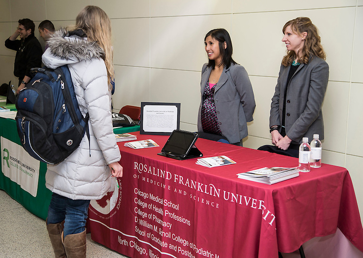 Amanda Noascono, left, and Ashley Ryan of the Rosalind Franklin University of Medicine and Science (RFUMS), talk with students about graduate school and career opportunities during the Science and Health Graduate School Forum Friday, Feb. 27, 2015 at DePaul University's Lincoln Park Campus.  Noascono is the Director of Admissions and Recruitment at Rosalind Franklin University and Ryan is an admissions counselor. (DePaul University/Jamie Moncrief)