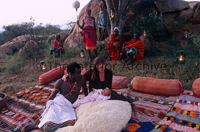 Anna and her husband Lemarti admire their brand new baby watched by a group of Masai