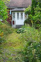 Traditional style Swedish wooden painted house. Overgrown unkempt garden. A veranda. Smaland region. Sweden, Europe.