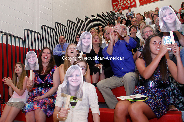 Southbury, CT-062113MK30 The family of Taylor Doyle holds pictures of her during Pomperaug High School class of 2013 commencement exercises on Friday evening at Pomperaug High School in Southbury. Michael Kabelka / Republican-American.