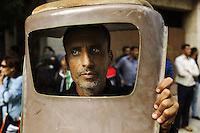 A man protects his head from flying debris using a chair as cover in Tahrir square