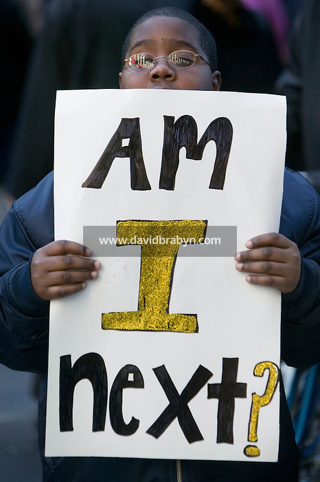 """16 December 2006 - New York City, NY - 10 year-old Khalix Phillips is seen on 34th street holding a sign that reads """"Am I next?"""" after marching down Fifth Avenue in New York City, USA, 16 December 2006, to protest the fatal police shooting of Sean Bell and the wounding of two of his friends in a 50-shot fusillade on his wedding day."""