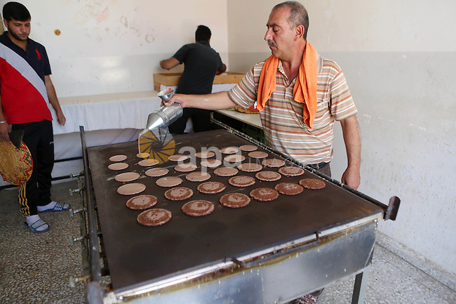 """A Palestinian man prepares traditional pancakes known as ''Qatayef"""" at his shop during the Muslim holy fasting month of Ramadan in the West Bank village of Ein Yabrud near Ramallah on June, 21, 2016. Ramadan is sacred to Muslims because it is during that month that tradition says the Koran was revealed to the Prophet Mohammed. The fast is one of the five main religious obligations under Islam. More than 1.5 billion Muslims around the world will mark the month, during which believers abstain from eating, drinking, smoking and having sex from dawn until sunset. Photo by Shadi Hatem"""