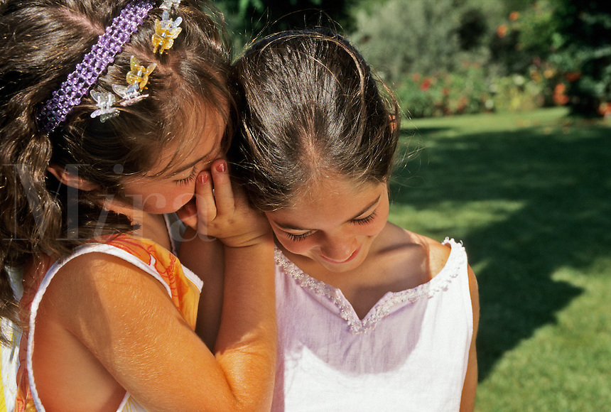 Two sisters aged seven 7, and nine, 9 years old, whispering, sharing a secret..