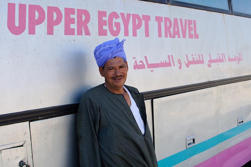 A passenger waits alongside a bus