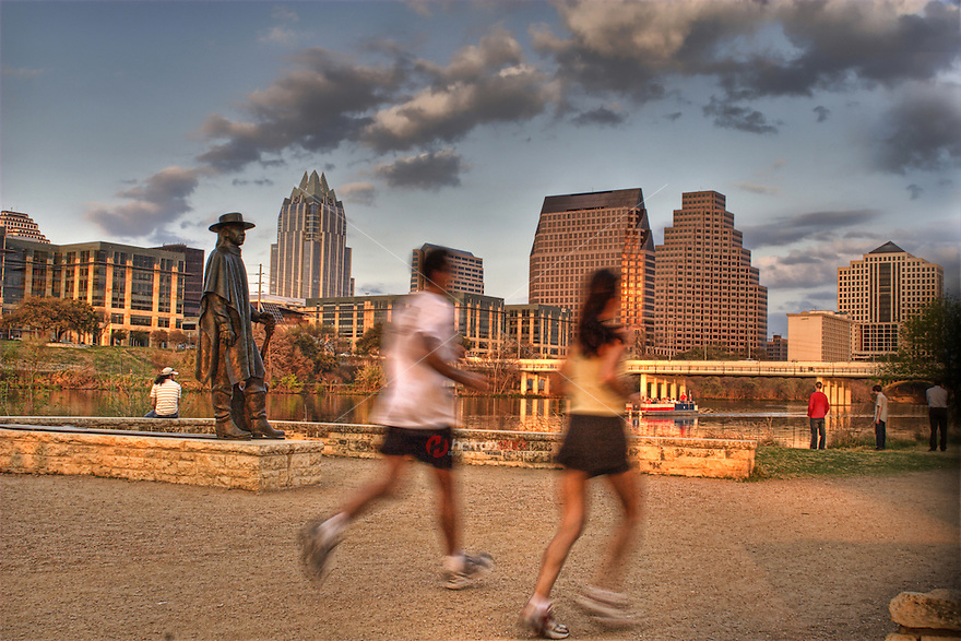 Runners and jogggers enjoy the hike and bike trail on Town Lake with Stevie Ray Vaughan Memorial and river boat in the foreground Austin, Texas, USA