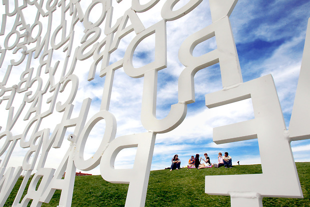"An early dismissal from school combined with pleasant weather made for perfect conditions for a hilltop picnic for a group of friends from North, Lincoln and Southeast Polk High Schools Wednesday at the Pappajohn Sculpture Park in downtown Des Moines.  The slope overlooks ""Nomade"" a 25-foot-tall sculpture built from randomly arranged stainless steel letters by Spanish artist Jaume Plensa.  ""We've driven by so many times and we have always said we wanted to come and have a picnic here,"" said Lindsey Schultz of Des Moines, one of the picnickers."