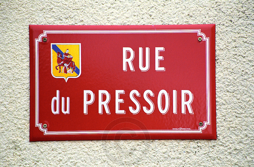A red street sign saying rue du Pressoir, the wine press street, on a stone wall, with an emblem showing Saint Martin, a patron saint of wine, Languedoc, Languedoc-Roussillon, France
