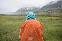 Hiker standing in rain in lush Tjäktjavagge near Sälka hut, Kungsleden trail, Lapland, Sweden