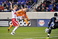 Geoff Cameron (20) of the Houston Dynamo takes a shot as Tim Ream (5) and goalkeeper Bouna Coundoul (18) of the New York Red Bulls defend. The New York Red Bulls  and the Houston Dynamo played to a 1-1 tie during a Major League Soccer (MLS) match at Red Bull Arena in Harrison, NJ, on April 02, 2011.