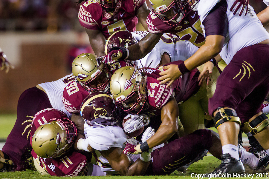 TALLAHASSEE, FLA. 9/5/15-Texas State University's running back Robert Lowe is stopped by Florida State University defenders Derrick Mitchell, Jr., left, Demarcus Christmas and Terrance Smith during first half action in the football game at Doak Campbell Stadium in Tallahassee.<br /> <br /> COLIN HACKLEY PHOTO