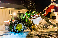 Removing snow at night in the fishing village of Reine in the Lofoten Islands, Arctic, Northern Norway. A week earlier the islands were paralyzed by the most snow to fall in 25 years.