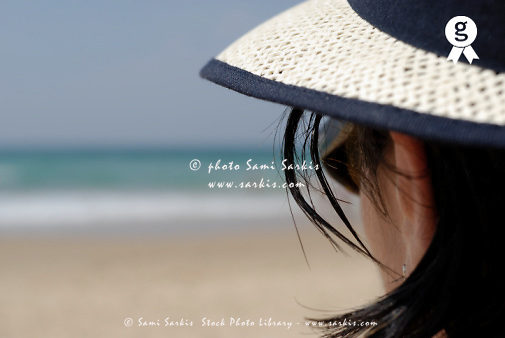 Woman wearing hat and glasses on beach, close-up, rear view (Licence this image exclusively with Getty: http://www.gettyimages.com/detail/200471713-001 )