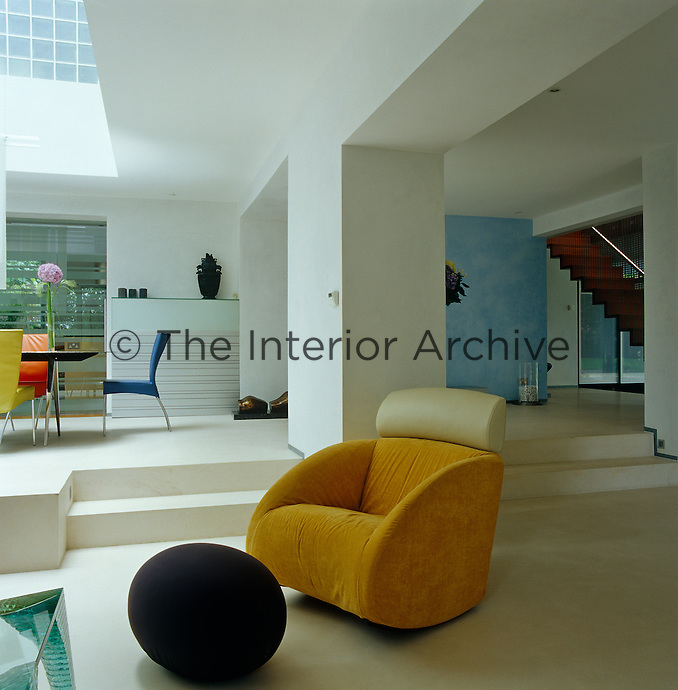 A yellow armchair and blue ball-like footstool in a corner of the living room which features polished limestone floors