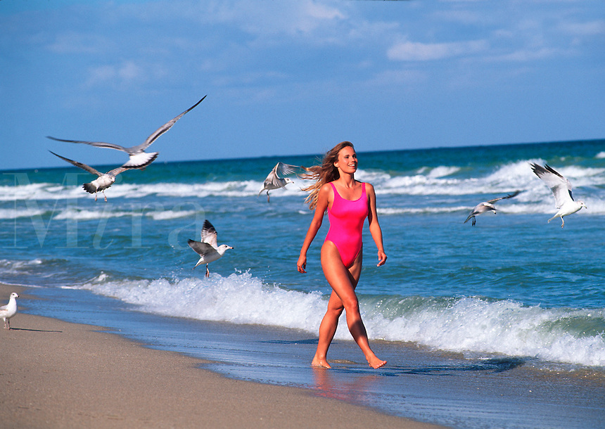 Young woman walking on the beach with seagulls