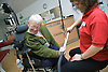 Fitness instructor at the gym helping woman to use equipment to strengthen upper body,