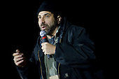 Kandahar, Afghanistan - December 17, 2009 -- Comedian Dave Attell performs at the 2009 USO Holiday Tour stop in Kandahar, Afghanistan, Thursday, December 17, 2009. United States Navy Admiral Mike Mullen, chairman of the Joint Chiefs of Staff, and his wife Deborah, welcomed tennis star Anna Kournikova, tennis coach Nicholas Bollettiere and musician Billy Ray Cyrus on the tour visiting troops in Afghanistan, Iraq and Germany. .Mandatory Credit: Chad J. McNeeley - DoD via CNP