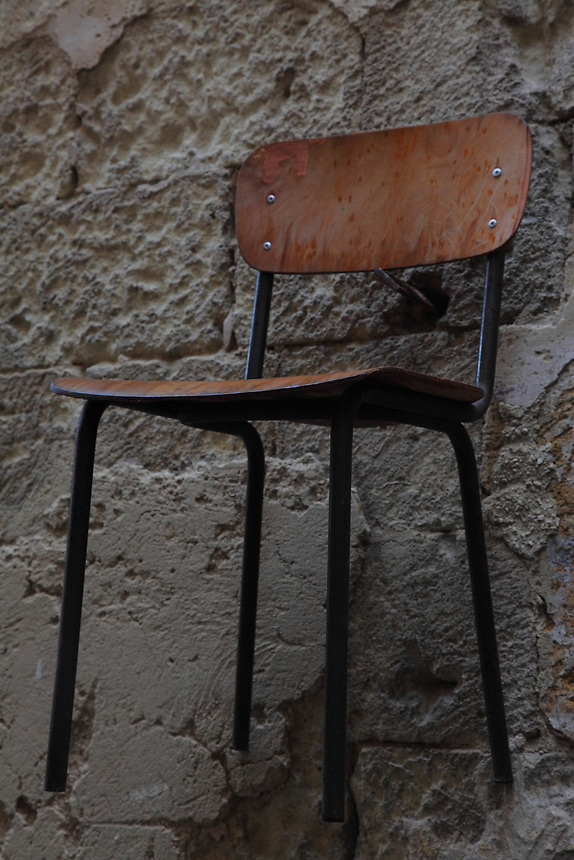 In the old part of the town of Taranto, the suggestive particular of a typical, simple, old chair that is hanged by a big iron nail to the external wall of an old building. Digitally Improved Photo.