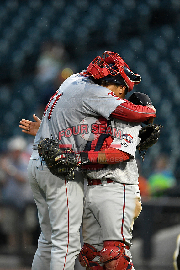 Pitcher Denyi Reyes (41) of the Greenville Drive gets a hug from catcher Isaias Lucena after posting the final out in a nine-inning complete-game shutout against the Columbia Fireflies on Sunday, May 27, 2018, at Spirit Communications Park in Columbia, South Carolina. Greenville won, 3-0. It was the first complete-game shutout in the South Atlantic League this season.(Tom Priddy/Four Seam Images)