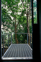 A balcony opens out into the garden which is set amongst mature trees