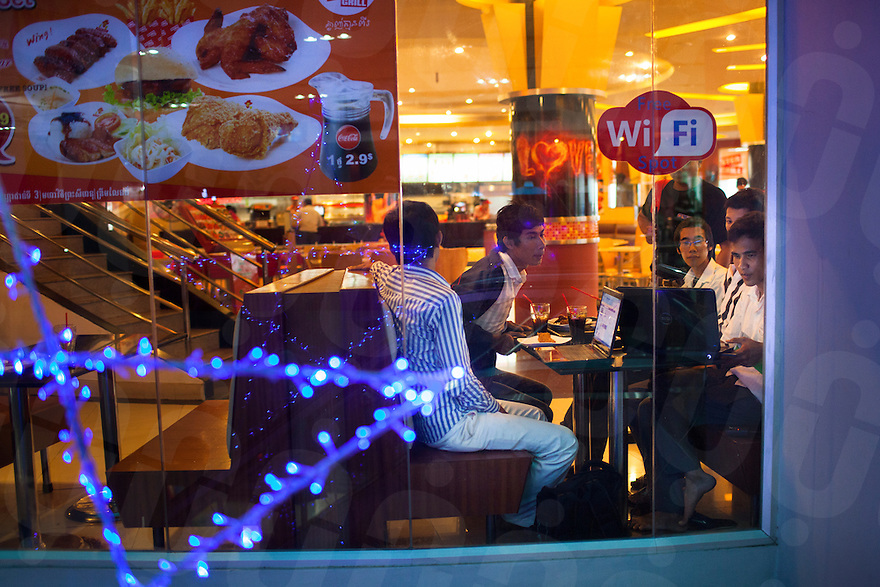 May 14, 2012 - Phnom Penh, Cambodia. Young people sit in a fast food chain in Soraya mall. © Nicolas Axelrod / Ruom