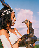 PERU, Iquitos, Amazon Rainforest, South America, Latin America, girl in traditional costume holding a snake in Iquitos.