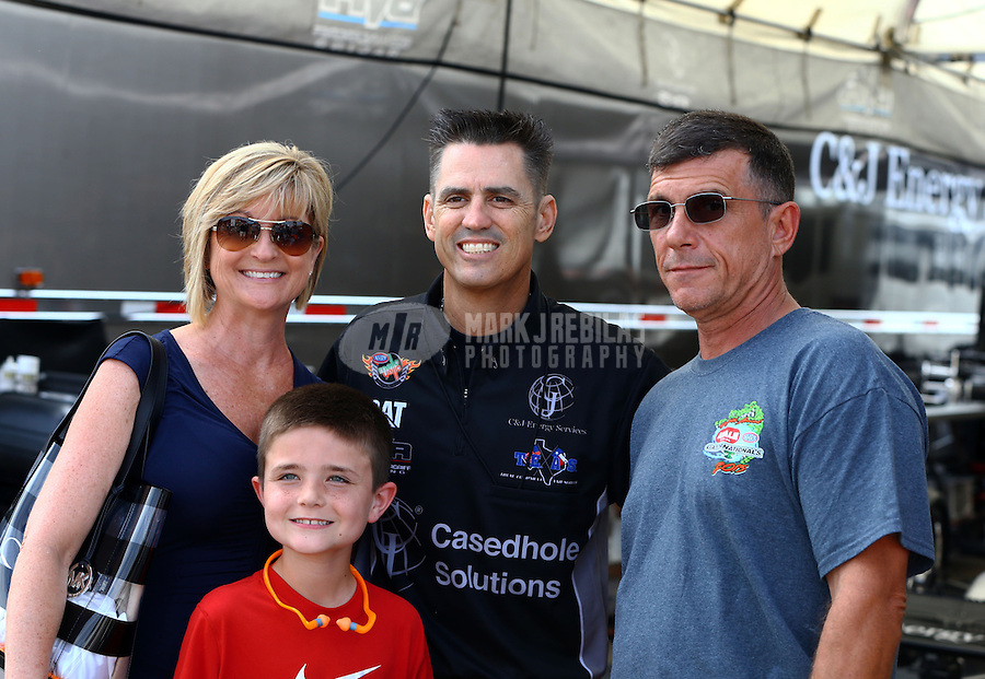 Mar 14, 2015; Gainesville, FL, USA; NHRA top fuel dragster driver Larry Dixon (center) poses for a photo with fans in the pits prior to qualifying for the Gatornationals at Auto Plus Raceway at Gainesville. Mandatory Credit: Mark J. Rebilas-