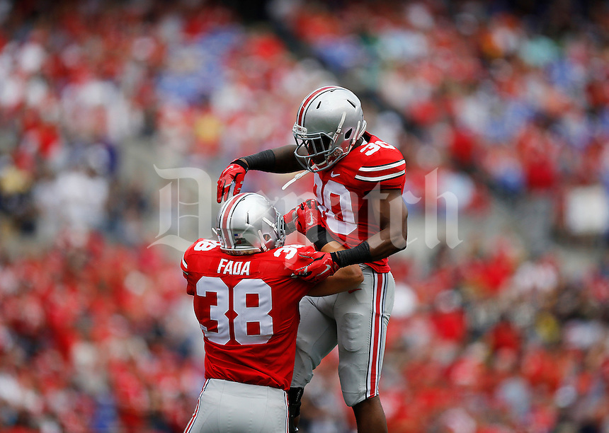 Ohio State Buckeyes linebacker Devan Bogard (30) and Ohio State Buckeyes linebacker Craig Fada (38) celebrate after a stop during the third quarter of the college football game between the Ohio State Buckeyes and the Navy Midshipmen at M&T Bank Stadium in Baltimore, Saturday afternoon, August 30, 2014. The Ohio State Buckeyes defeated the Navy Midshipmen 34 - 17. (The Columbus Dispatch / Eamon Queeney)