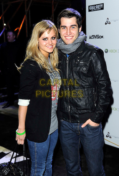 "TINA O'BRIEN & JARED MURILLO.Launch party for new video game ""Call Of Duty: Black Ops"", Battersea Power Station, London, England, UK. .November 8th, 2010.half length jeans denim jacket black grey gray top leather scarf couple coke print.CAP/DH.©David Hitchens/Capital Pictures."