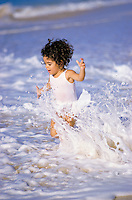 A young girl runs through waves at the shoreline of a beach on Oahu.