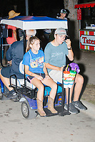 People ride a golf cart at the Iowa State Fair in Des, Moines, Iowa, on Sun., Aug. 11, 2019.