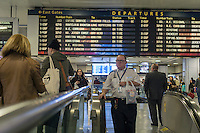 Travelers for Amtrak and NJ Transit in Penn Station in New York on Friday, October 14, 2016 wait by the departure board. Amtrak has started to bring Penn Station into the 21st Century installing digital boards, seen behind older board, in various parts of the station in part to relieve the congestion that occurs around the board. (© Richard B. Levine)