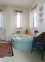 Narrow windows hung with Venetian blinds surround the bathroom, while patterned textiles bringroom a touch of bolder colour to the space