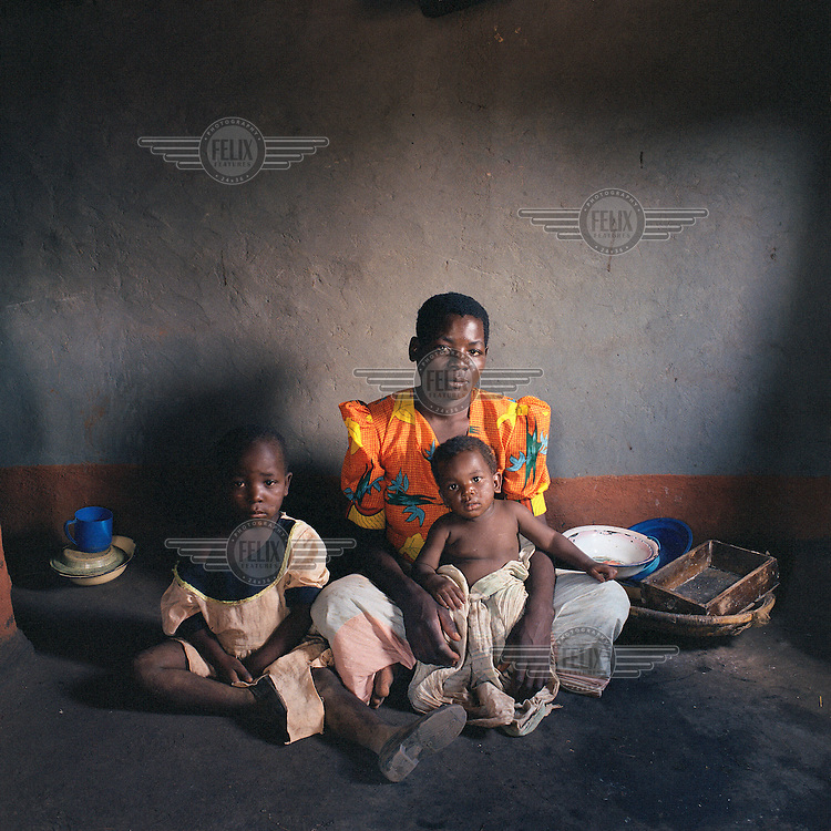 Joyce Foliasi (27) with daughters Ndaziona (six) and Yankho (11 months). Ndaziona means: 'I have a lot of worries'. Yankho is the local word for 'answer'. Joyce is HIV positive and the only villager to be open about it.