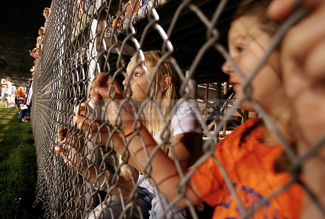 Madison May, 10, and her cousin Makayla May, 6, watch from under the bleachers as Pike County Central High School's 2009 homecoming queen contestants are introduced at the homecoming football game.