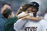 Marcus Nettles of the Lake Elsinore Storm gets a hug from a young fan before a California League 2002 season game at The Diamond, in Lake Elsinore, California. (Larry Goren/Four Seam Images)