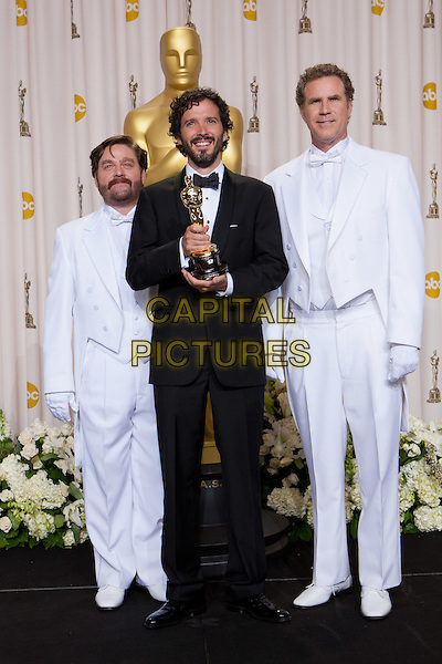 "Bret McKenzie, Oscar® winner for Achievement in Music Written for Motion Pictures (Original Song) for ""Man or Muppet"" from ""The Muppets"", poses backstage with Zach Galifianakis and Will Ferrell during the live ABC Television Network broadcast of the 84th Annual Academy Awards® from the Hollywood and Highland Center in Hollywood, CA, Sunday.*Editorial Use Only*.oscars award trophy winner full length black tuxedo white suit.CAP/A.M.P.A.S./NFS.©A.M.P.A.S. Supplied by Capital Pictures."