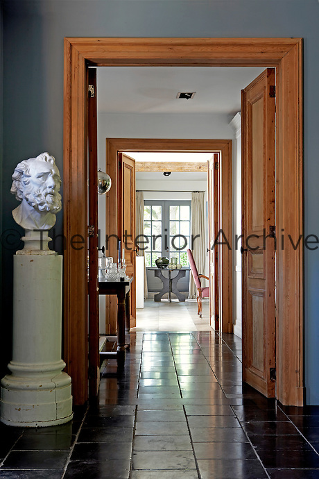 A Roman bust stands guard in the entrance hall at one end of an enfilade leading to the kitchen