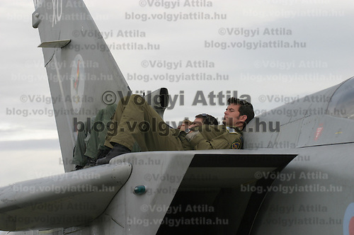 Soldiers take a break lying on the wing of an A7 Tornado fighter jet during the International Air Show held in Kecskemet.