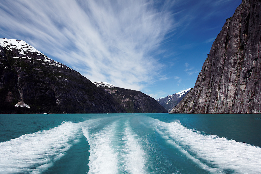 Sheer-walled mountains rise above boat wak in Tracy Arm, Southeast Alaska, USA