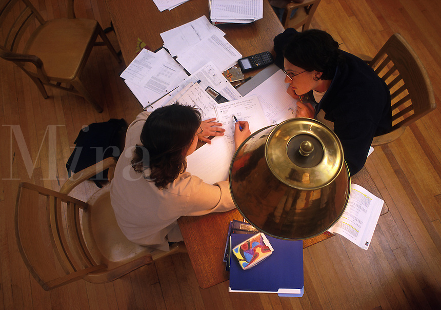 Overview of female college students studying at a table full of books and papers. Wesleyan University.