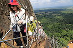 People climbing metal staircase ascending to rock palace fortress, Sigiriya, Central Province, Sri Lanka, Asia