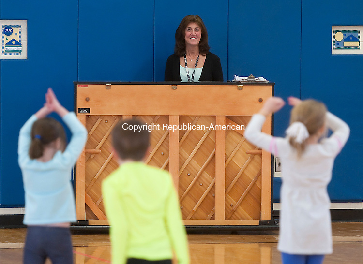 MIDDLEBURY, CT--- -010716JS08--Melody McVerry, a physical education teacher at Long Meadow Elementary School in Middlebury, plays piano as her kindergartner class as they stretch during class on Thursday. McVerry was named the Connecticut Elementary School Physical Education Teacher of the year by the Connecticut Association for Health, Physical Education, Recreation and Dance. <br /> Jim Shannon Republican-American