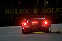 The #63 Ferrari of Toni Vilander, Olivier Beretta, and Andrea Bertolini races through a turn at night during the Rolex 24 at Daytona, Daytona International Speedway, Daytona Beach, FL, January 2011.  (Photo by Brian Cleary/www.bcpix.com)