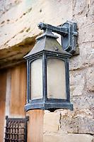 A wall lantern illuminates an entrance door to the property